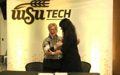 WSU Tech President Sheree Utash and dean of WSU's business school Larissa Genin hug after signing.