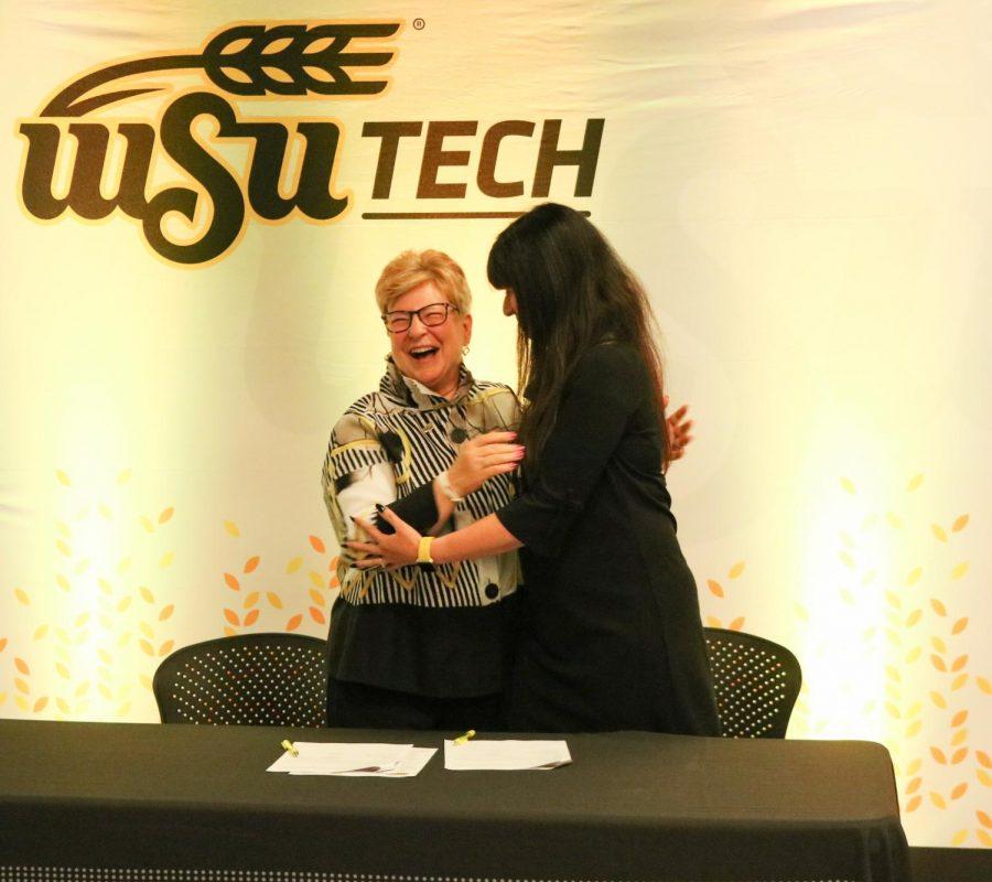 WSU Tech President Sheree Utash and dean of WSUs business school Larissa Genin hug after signing.