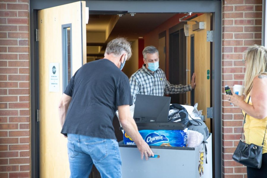 President Rick Muma and his husband help students along with their parents to move into Shocker Hall at WSU on August 13