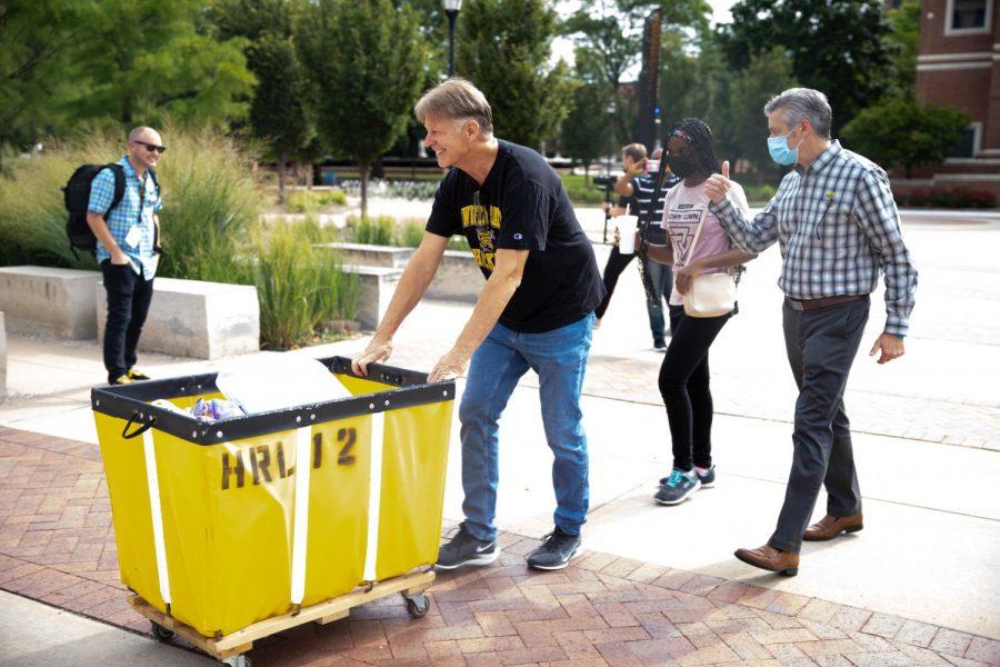 President Rick Muma and his husband help students move into Shocker Hall at WSU on August 13