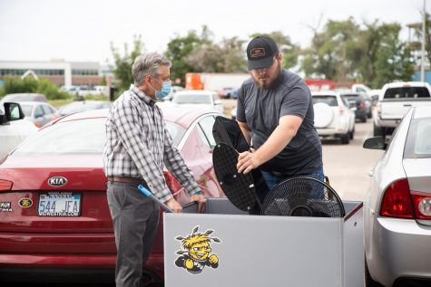 President Rick Muma helps students load up their belongings to move into The Flats at WSU on August 13