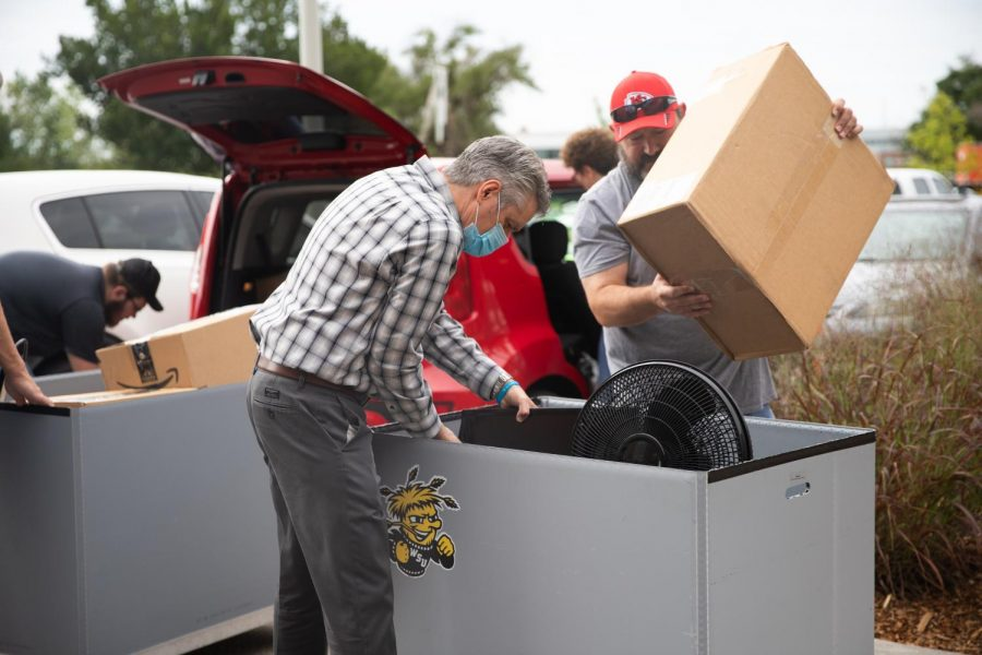 President Rick Muma and his husband help students and their families move into The Flats at WSU on August 13