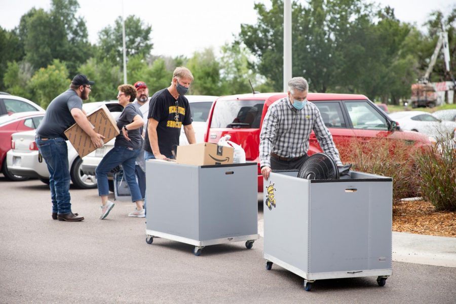 President Rick Muma and his husband help students move into The Flats at WSU on August 13