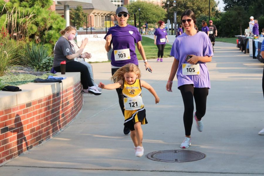 Young girl skips through the finish line during a Suspenders4Hope event at the Wichita State Student Rhatigan Student Center on Sept 11.